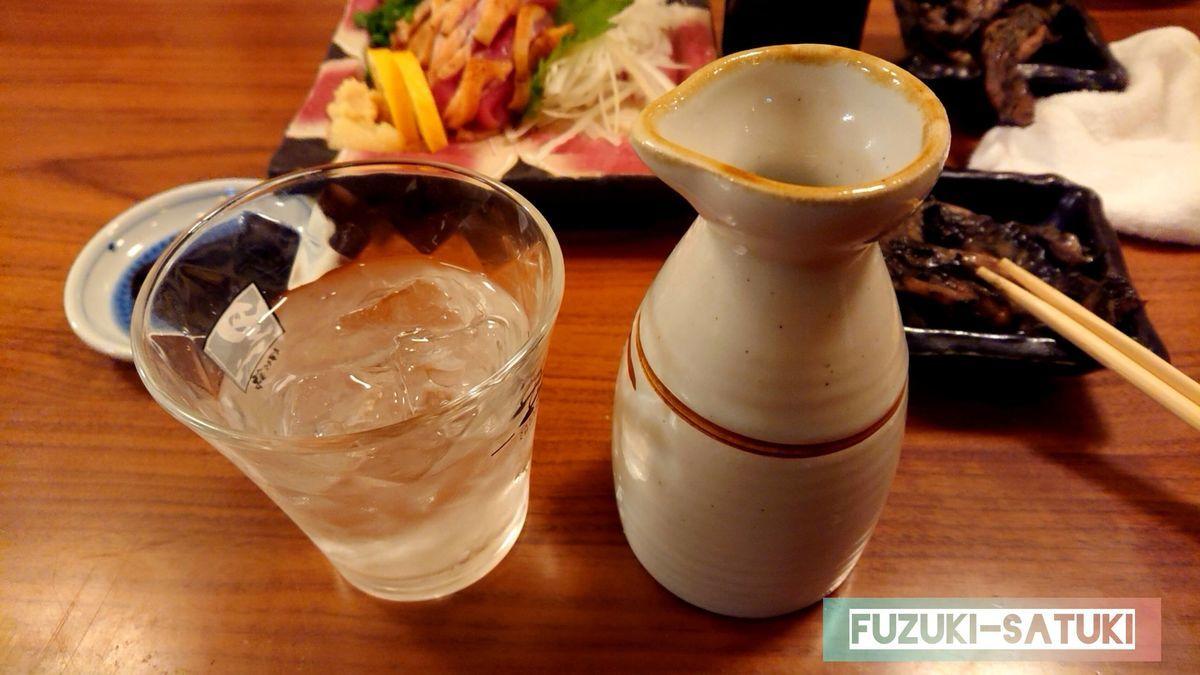 鶏の刺身と徳利と芋焼酎の注がれたグラス。鹿児島の地物は最高です。