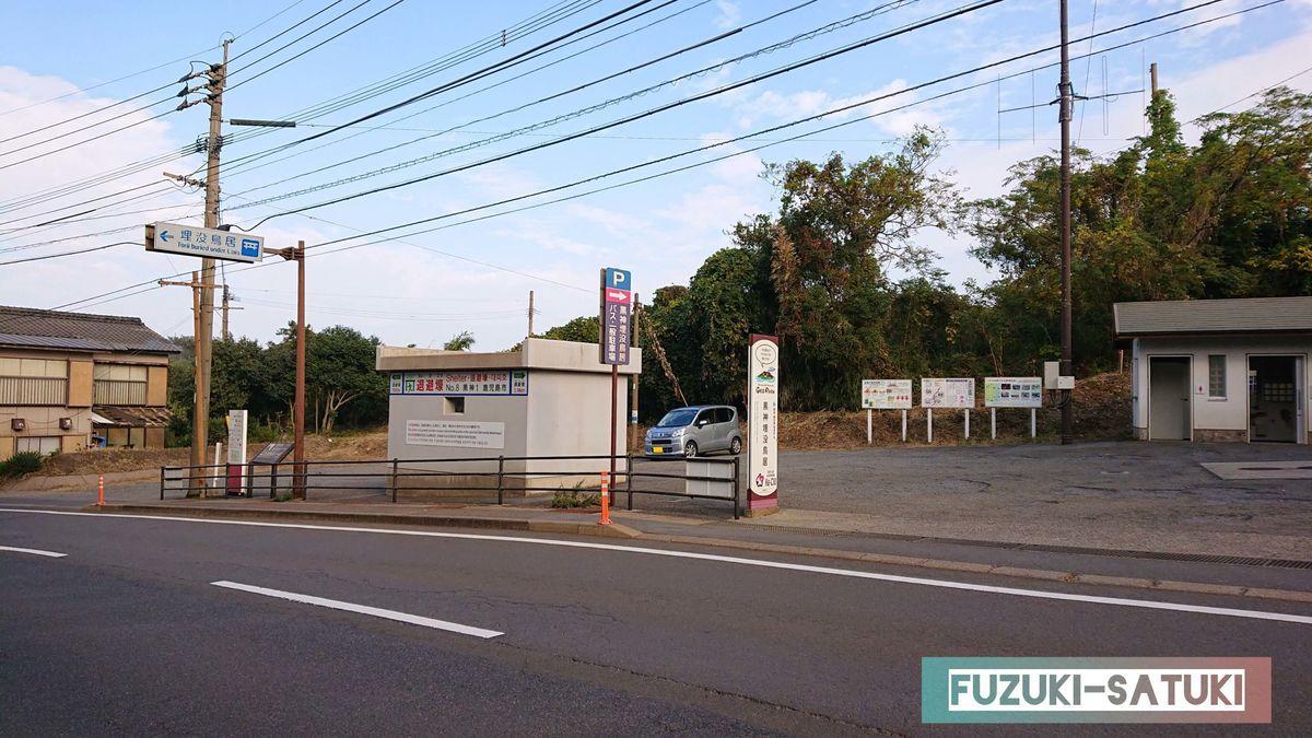 鹿児島県桜島にある黒神中学校前から黒神埋没鳥居へ向かう道中。退避壕とその看板、道向かいに広い砂利の駐車場と男女別のトイレがあるのが分かる。