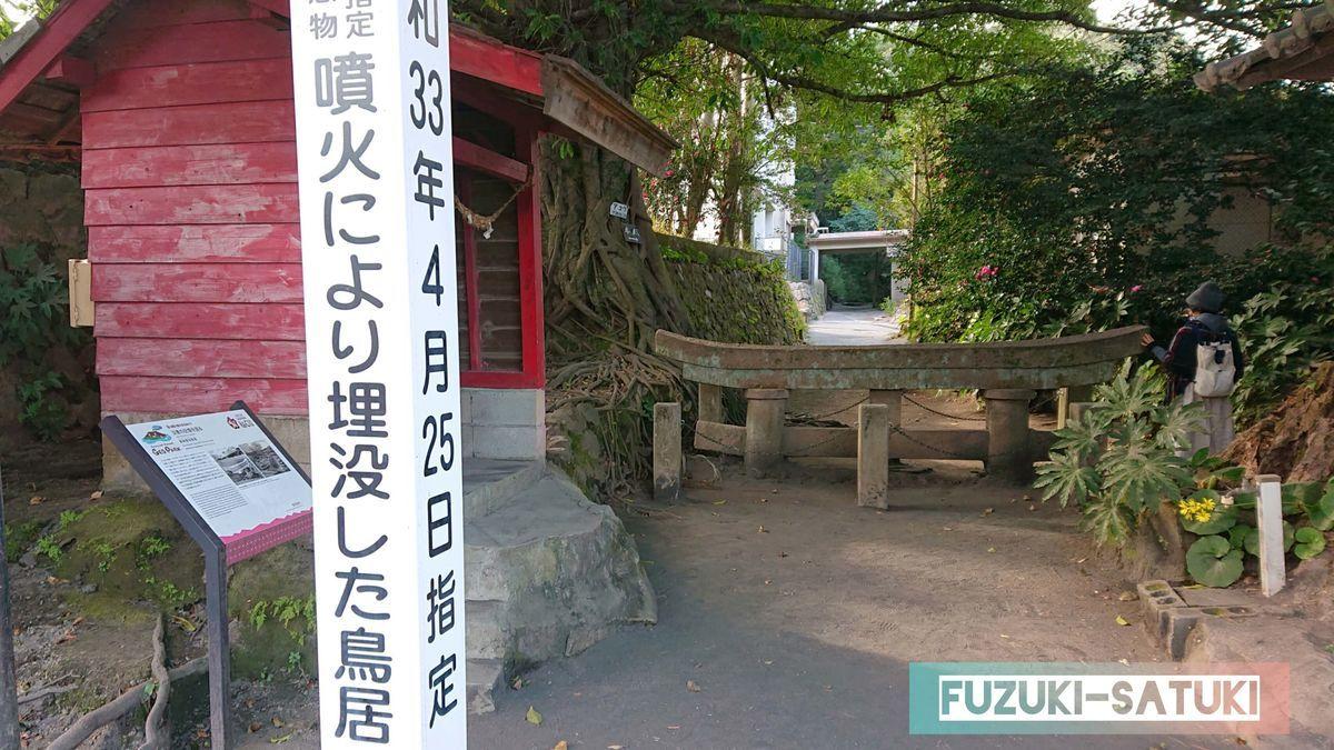 鹿児島県桜島にある埋没鳥居の入り口付近。道路沿いからも見えるそれは、ガードレールほどの高さしか出ていない鳥居の姿。