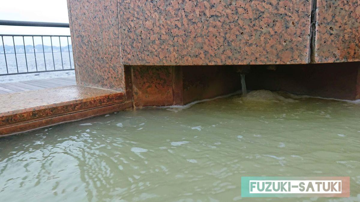 「桜島」溶岩なぎさ公園足湯の源泉口のひとつ。視線に入りづらい、配慮された場所から源泉が掛け流されていて、全長約100mのどこで入ってもほぼ一定の温度になるように設定されている。国民宿舎レインボー桜島と同じ濃厚な塩化物泉。