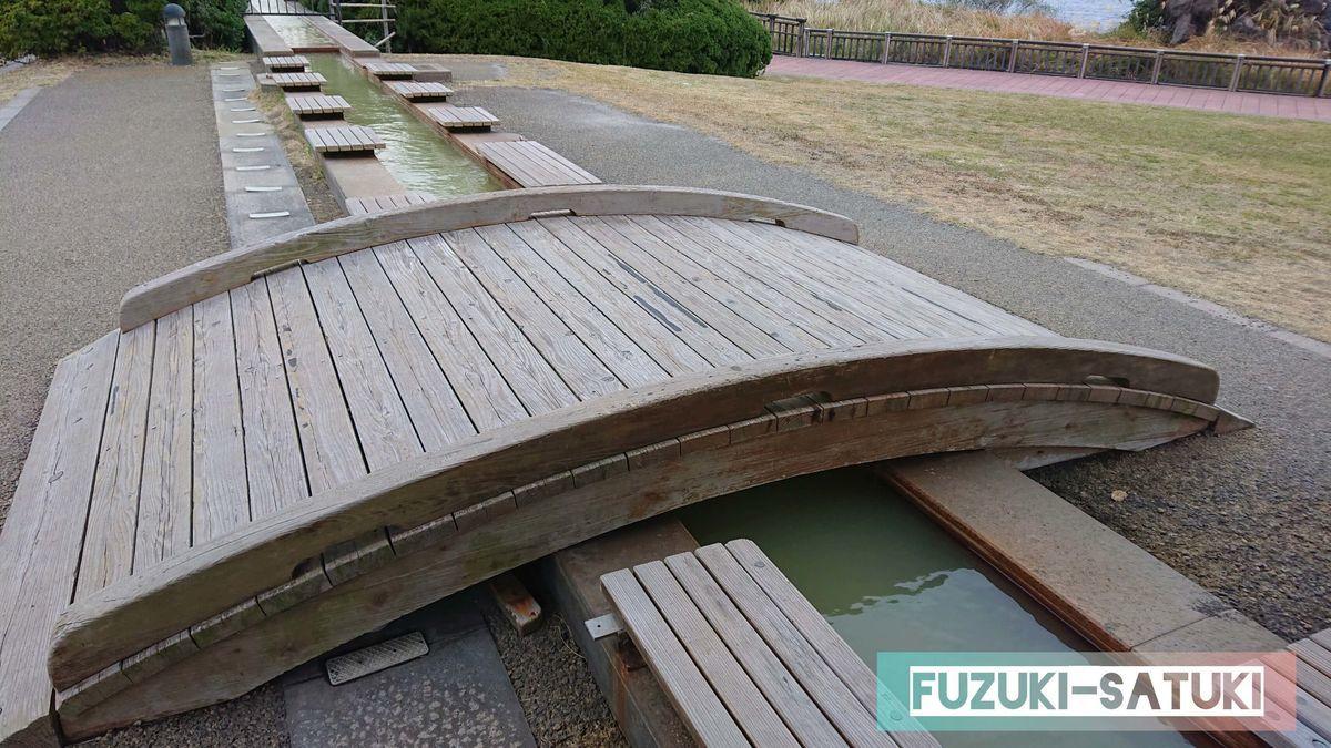 鹿児島県にある「桜島」溶岩なぎさ公園足湯の様子。木の樋のような造りで、両側から入ることができる。木の渡橋が趣を感じる。全長約100mあり、国民宿舎レインボー桜島と同じ源泉を掛け流している。