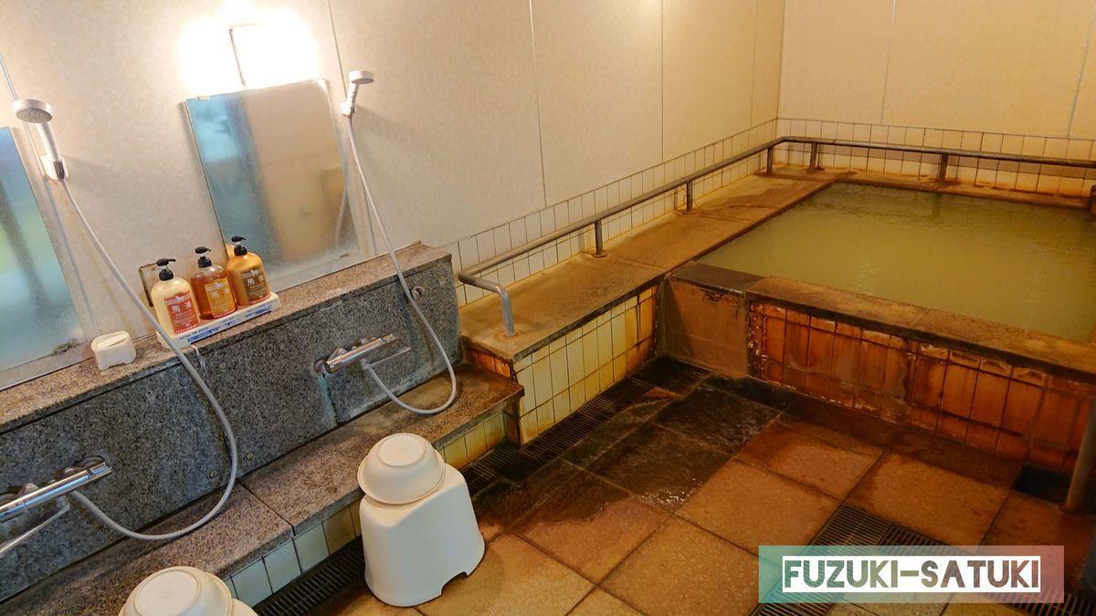 桜島マグマ温泉の洗い場と浴槽。洗い場は2つ、3人がゆっくり入れそうな大きさの浴槽の周りには手すりが囲むように付けられている。シャワーとカラン、シャンプー、コンディショナー、ボディーソープが備え付けられている。