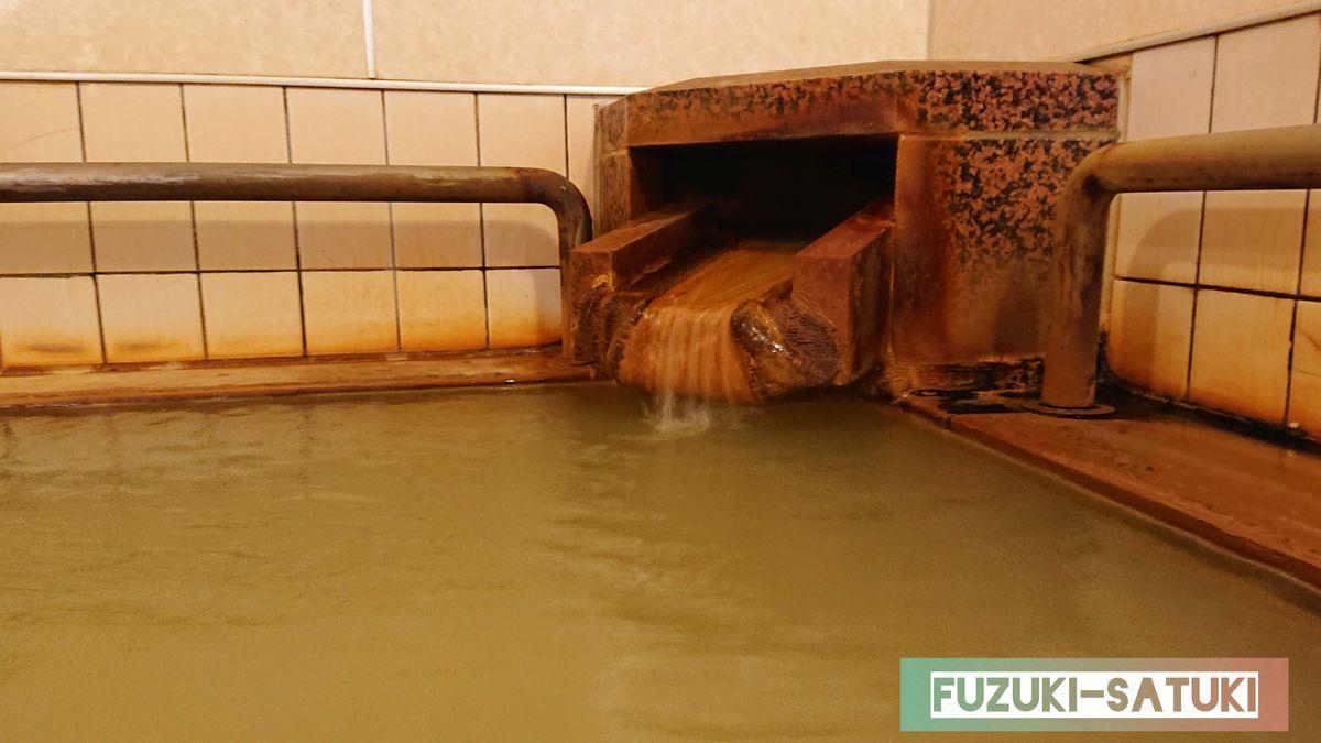 桜島マグマ温泉の浴槽から眺める源泉口。赤錆のように成分がこびり付いた湯口から、出口付近は透明に近い、湯船は濃厚な茶褐色のお湯だとわかる。