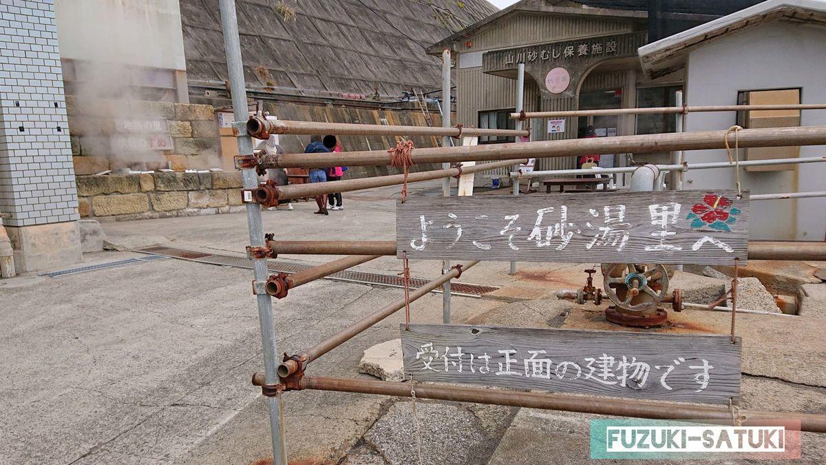 山川砂むし温泉『砂湯里』入り口から。ようこそ砂湯里へ。受付は正面の建物です。と書かれている。本館と、その左側に蒸し料理が売られている。