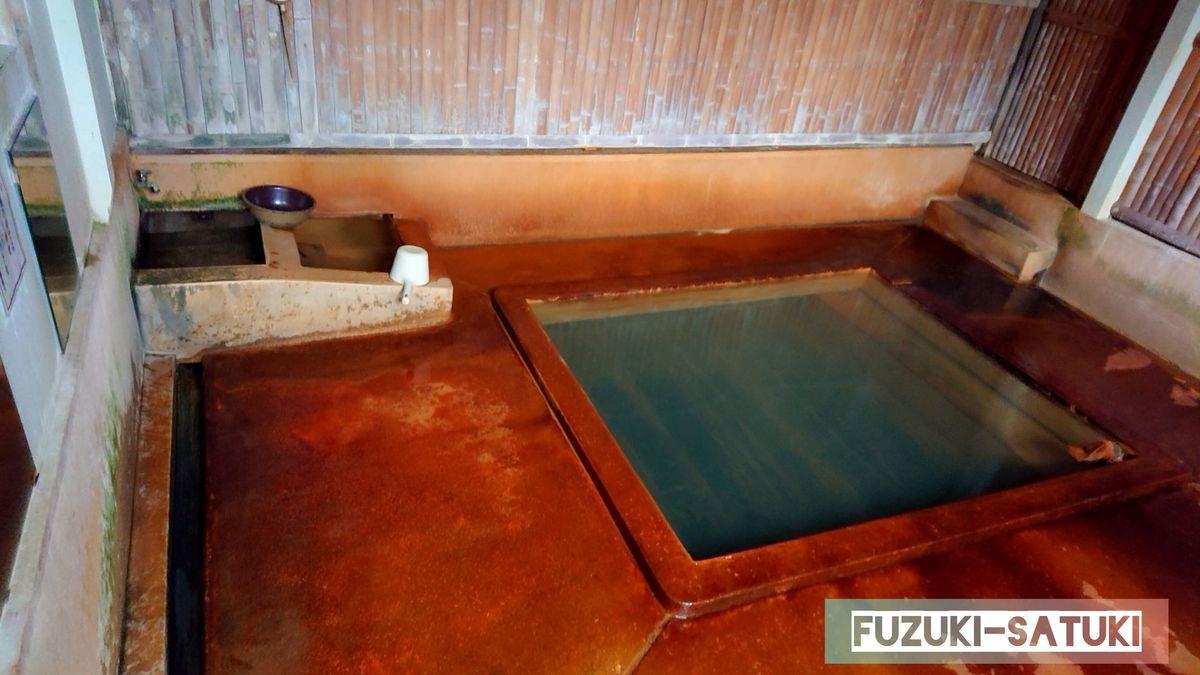 鹿児島県指宿市にある共同浴場のひとつ、弥次ヶ湯温泉の男湯の様子。薄緑に濁ったお湯。木枠の浴槽は4人位入れる大きさ。タオルの巻かれた塩ビパイプより源泉が出ている。浴槽とは別に、女湯と繋がっている掛け湯と、掛け水だろうか、蛇口の下には冷たい水が溜められている。