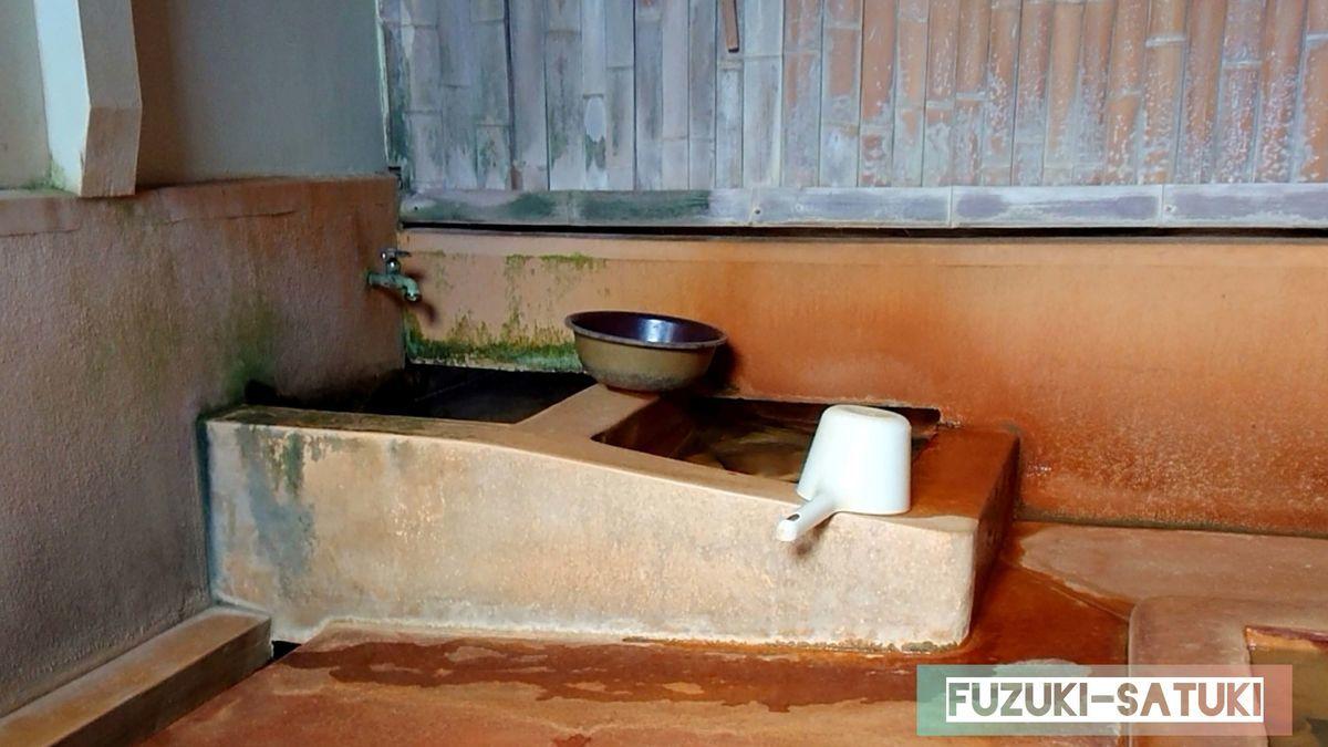 弥次ヶ湯温泉の男湯の掛け水と掛け湯。掛け湯は女湯と繋がっている様子。