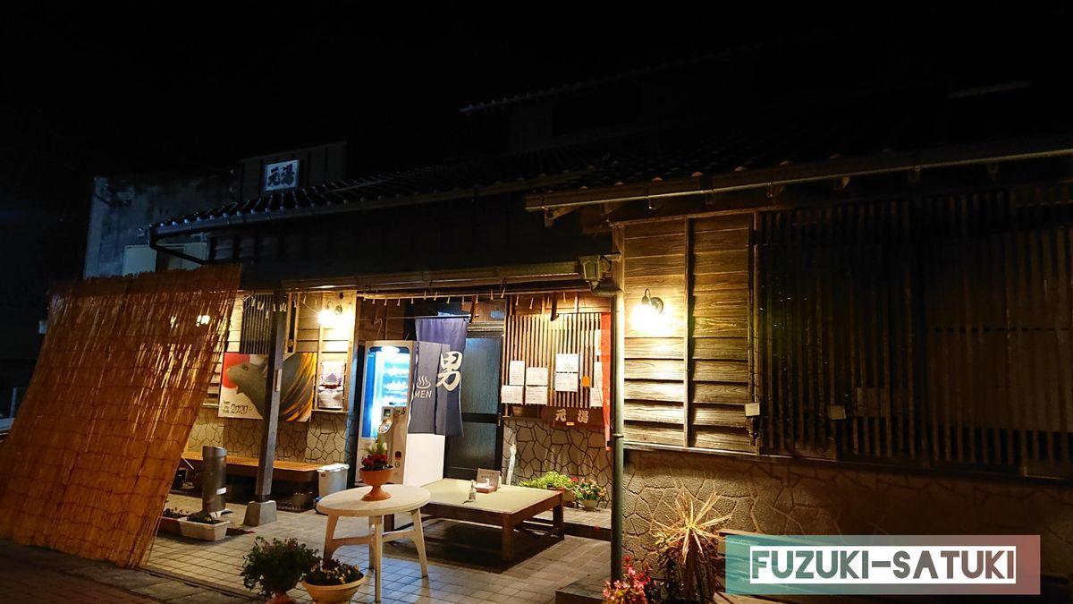 鹿児島県指宿市にある、指宿温泉発祥ともいわれる元湯温泉外観(夜)。レトロな木製の外観に優しい淡い黄色電球の灯りが雰囲気を醸し出している。