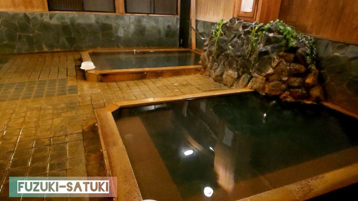 鹿児島県指宿市にあるいぶすき元湯温泉の男湯の様子。全体的に黄土色のタイルとコンクリートで作られた浴槽。源泉湯口は石を積まれた隙間から染み出ているような演出。浴槽のお湯は、薄緑の濁りのあるお湯。底が薄っすら見える透明さもある。
