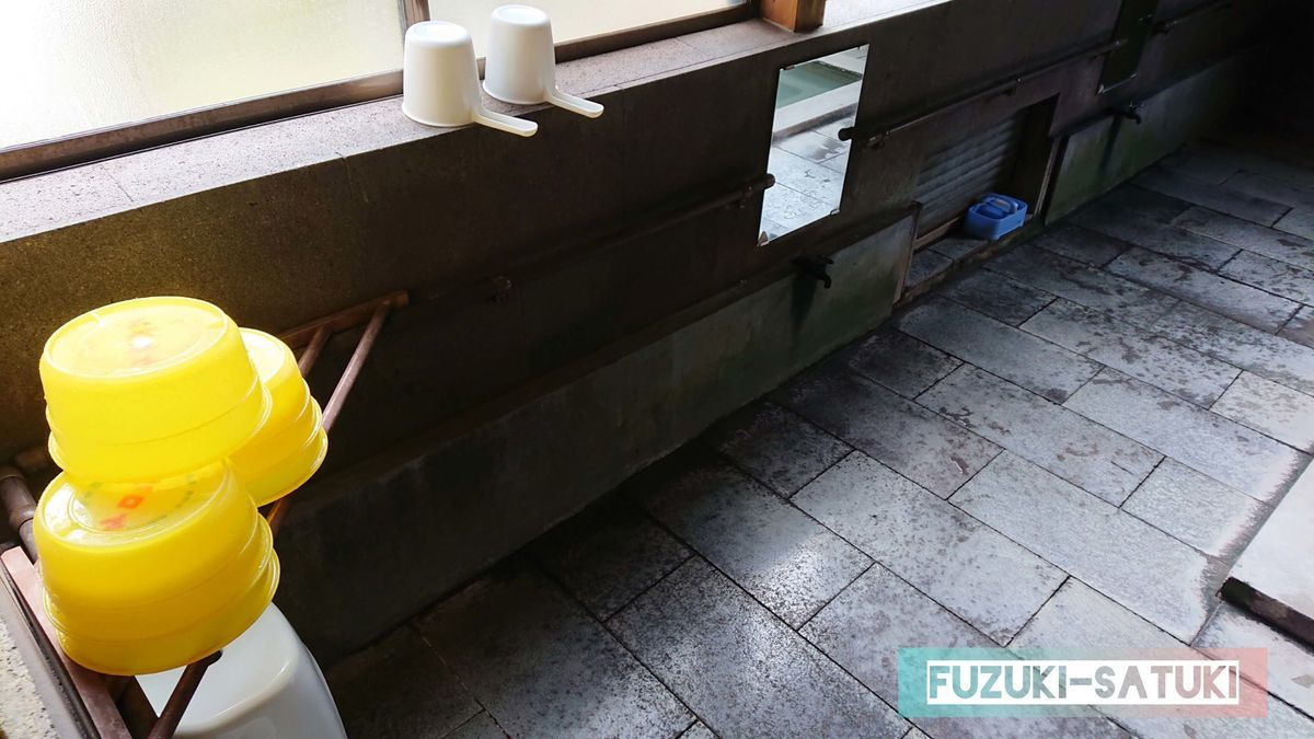 栗野岳温泉 南州館 桜湯にて。お湯は硫黄香る綺麗な乳白色。そこに綺麗に積まれているケロリン桶は、陽射しに輝く黄金色。