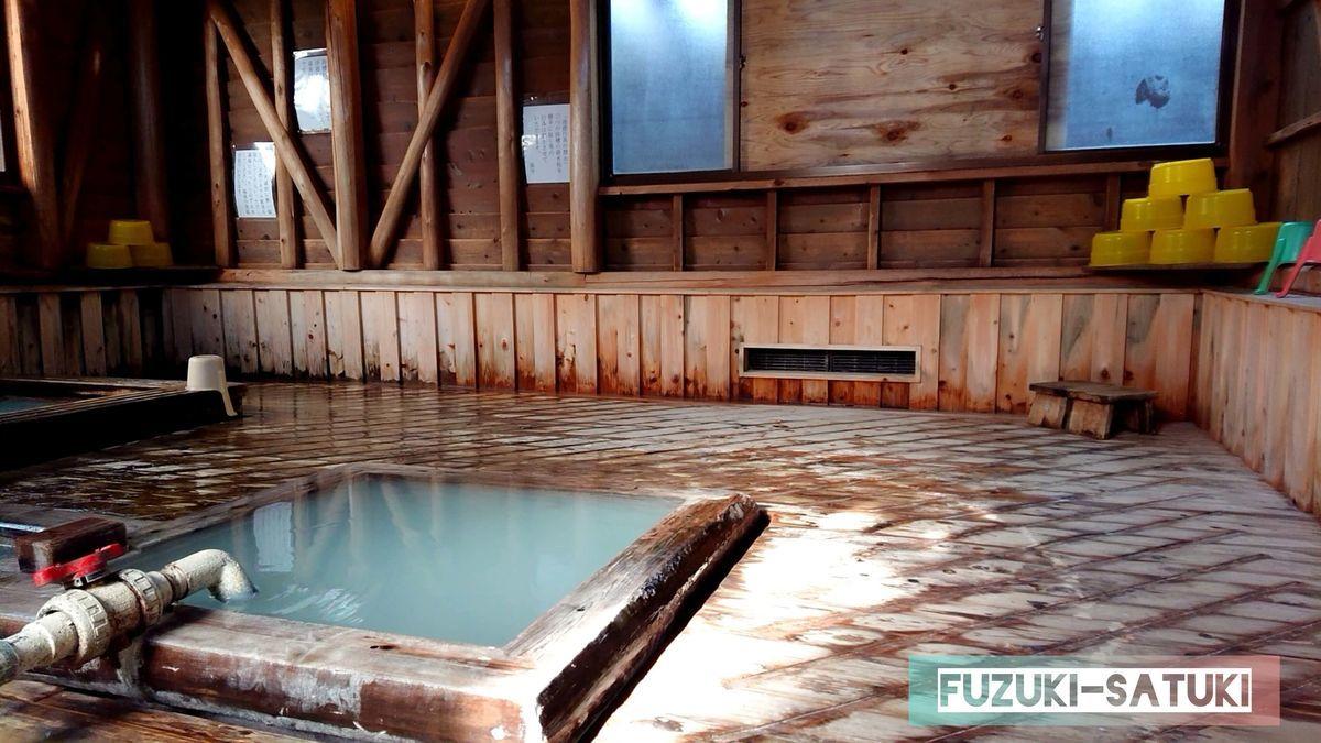 桐島湯之谷温泉 湯之谷山荘の男湯の様子。写真に写っているのは30℃程度の炭酸泉と、奥には綺麗に山積みされたケロリン桶。全体的に木で造られていて、硫黄と共に木の香りが心地良い。