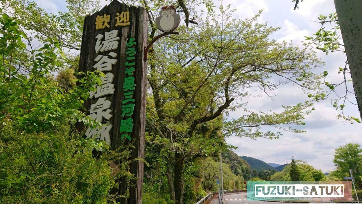 愛知県新城市にある、湯谷温泉郷入り口の看板。新緑に木の造り、味わいを感じる。