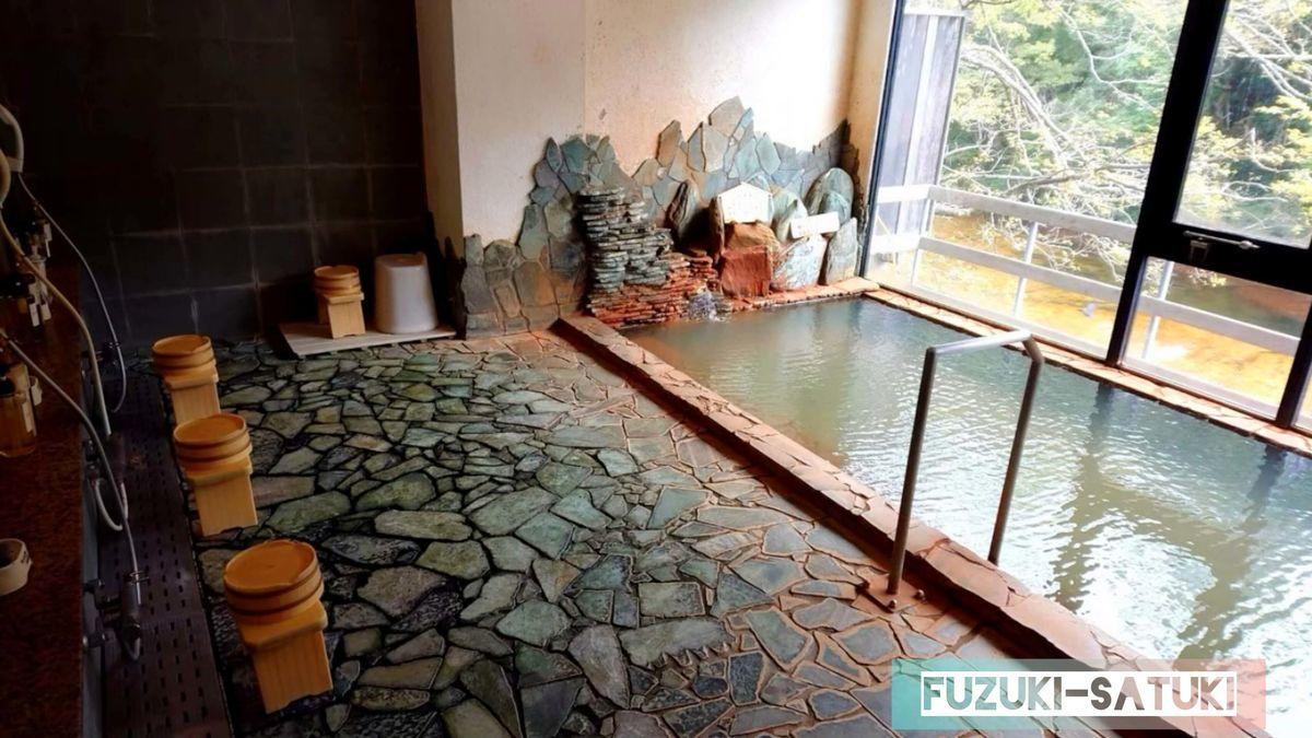 湯谷観光ホテル泉山閣 ほのくにの湯 内湯の様子。積み上げた岩の隙間からお湯が掛け流されている。足元は岩のタイル張り、浴槽も石で造られている。注がれているお湯は、周辺を赤く染め上げているにもかかわらず、土色のような緑がかった濁りのように見える。