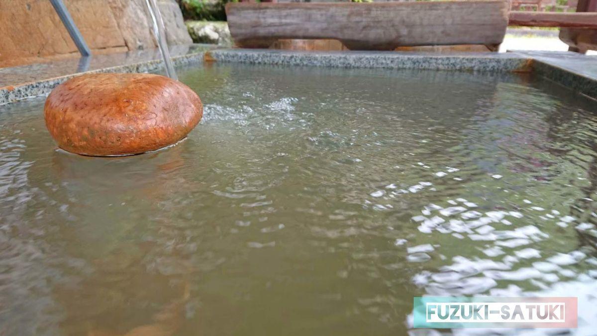 湯谷温泉の無料足湯の様子。ドボドボと濃厚な源泉が注がれている。