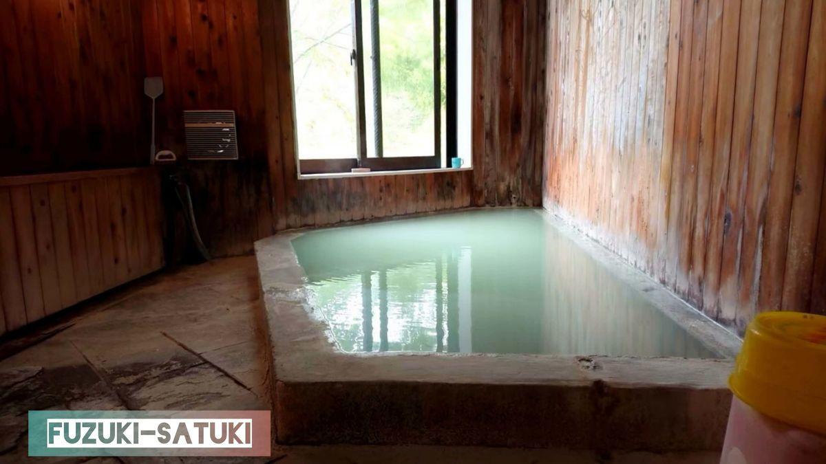 大出館 貸切風呂の様子。五色の湯が掛け流され、この日は濃厚な乳白色。木造の壁に囲われ、6人程が入れる石造りの浴槽がひとつあるのみ。洗い場はあるものの、カランひとつ、ボディーソープと思われる液体が置いてある。