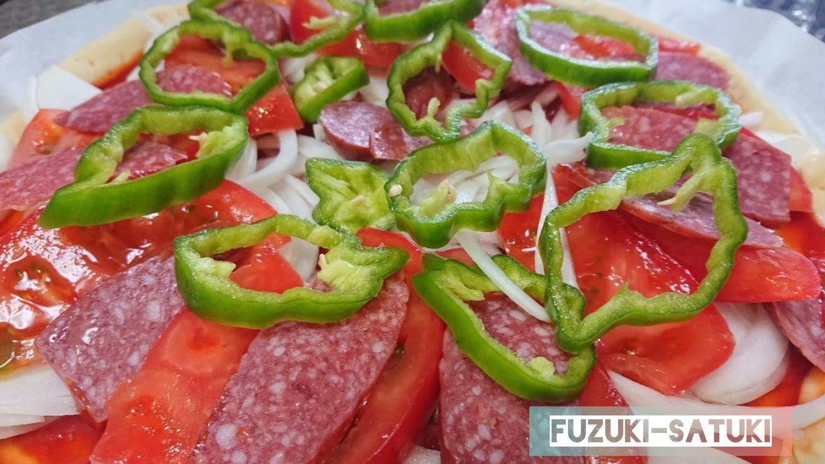 嫁のさつき手作りのピザ生地に、サラミ、玉ねぎ、ピーマンを乗せる。