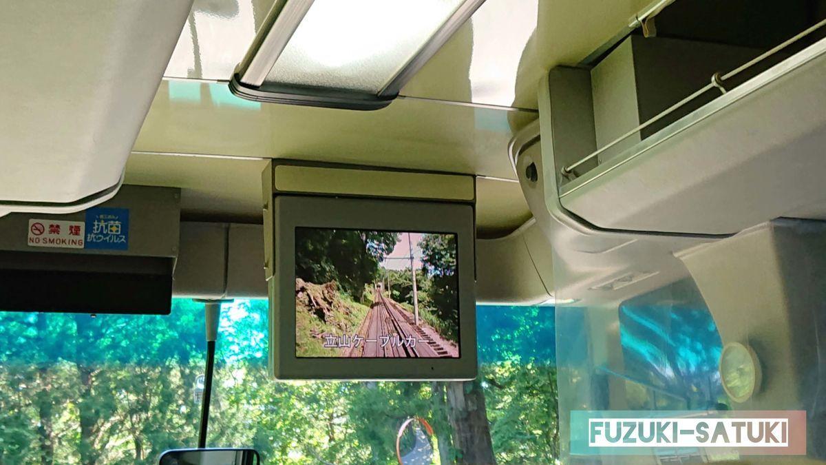 立山高原バス車内にて、運行中に前方のTVモニターにて立山の名所の説明がなされている。