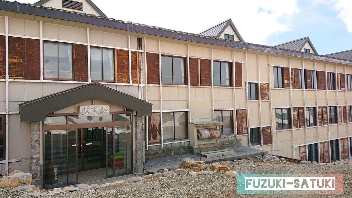 雷鳥荘、正面からの外観の様子。木とコンクリートで作られた地上2階建て(地下あり)の窓には、木製の頑丈そうな雨戸のようなものが設置されている。