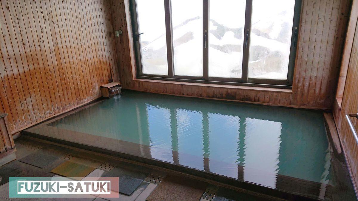 雷鳥荘にある展望風呂の様子。硫黄香る乳白色に、窓からは雪化粧した立山連峰が望める。