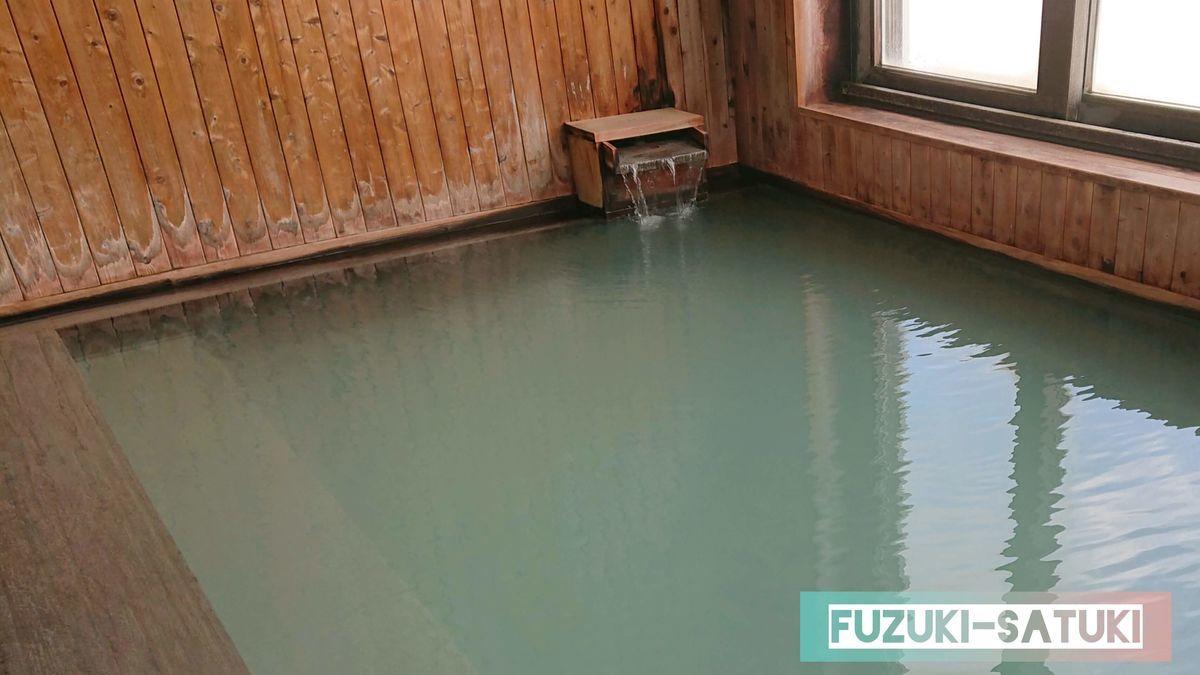 雷鳥荘にある男湯の展望風呂の様子。緑がかった乳白色の浴槽に源泉が流れ込んでいる。
