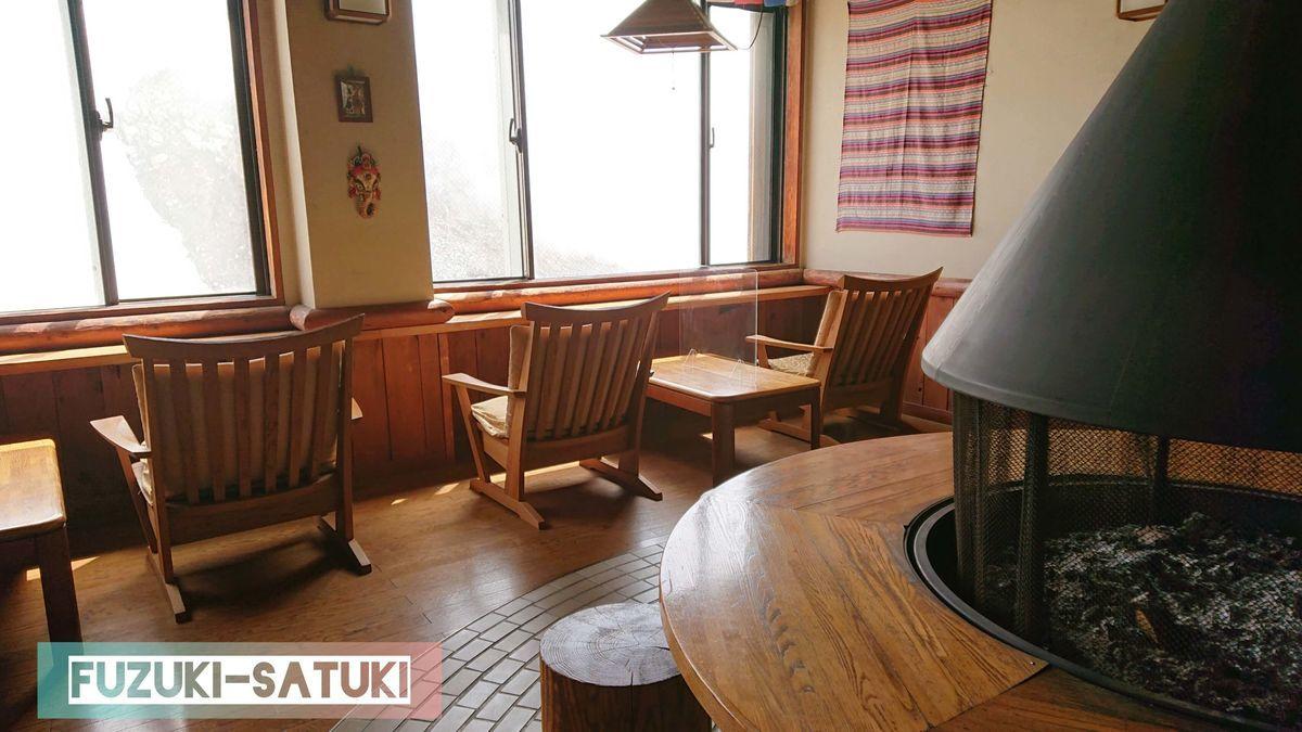 雷鳥荘の待合室の様子。暖炉を囲むように、木造のテーブル・椅子と。窓からは地獄谷がモクモクとしているのが見える。