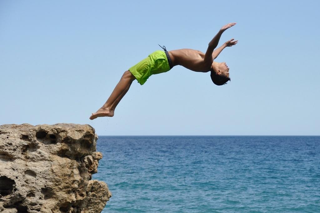 崖から海へ飛び込もうとしている男性