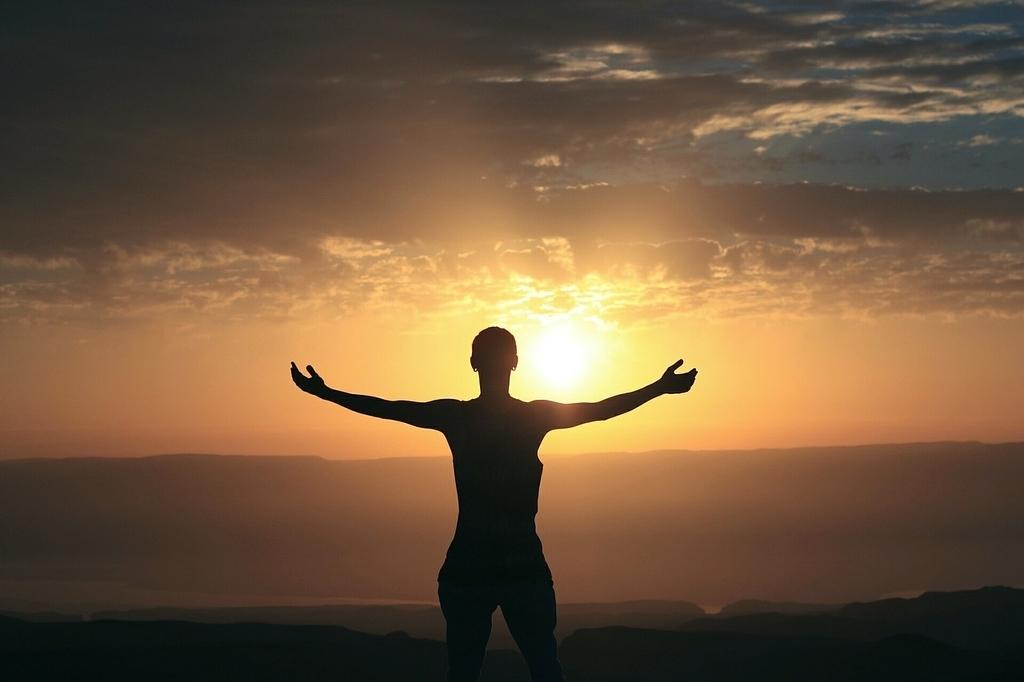 夕陽に向かい手を大きく広げる人