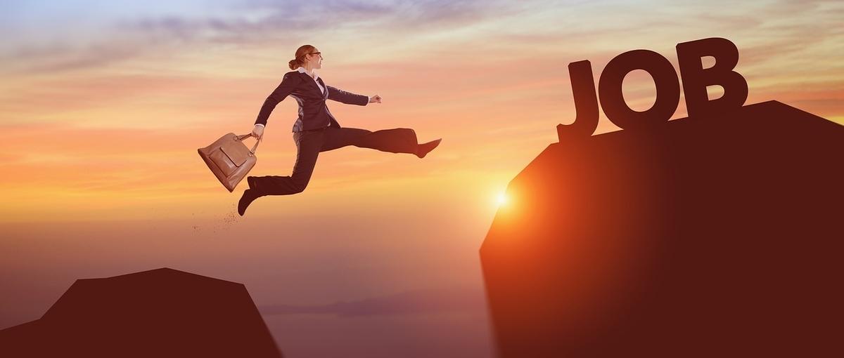 スーツ姿で前向きにジャンプする女性