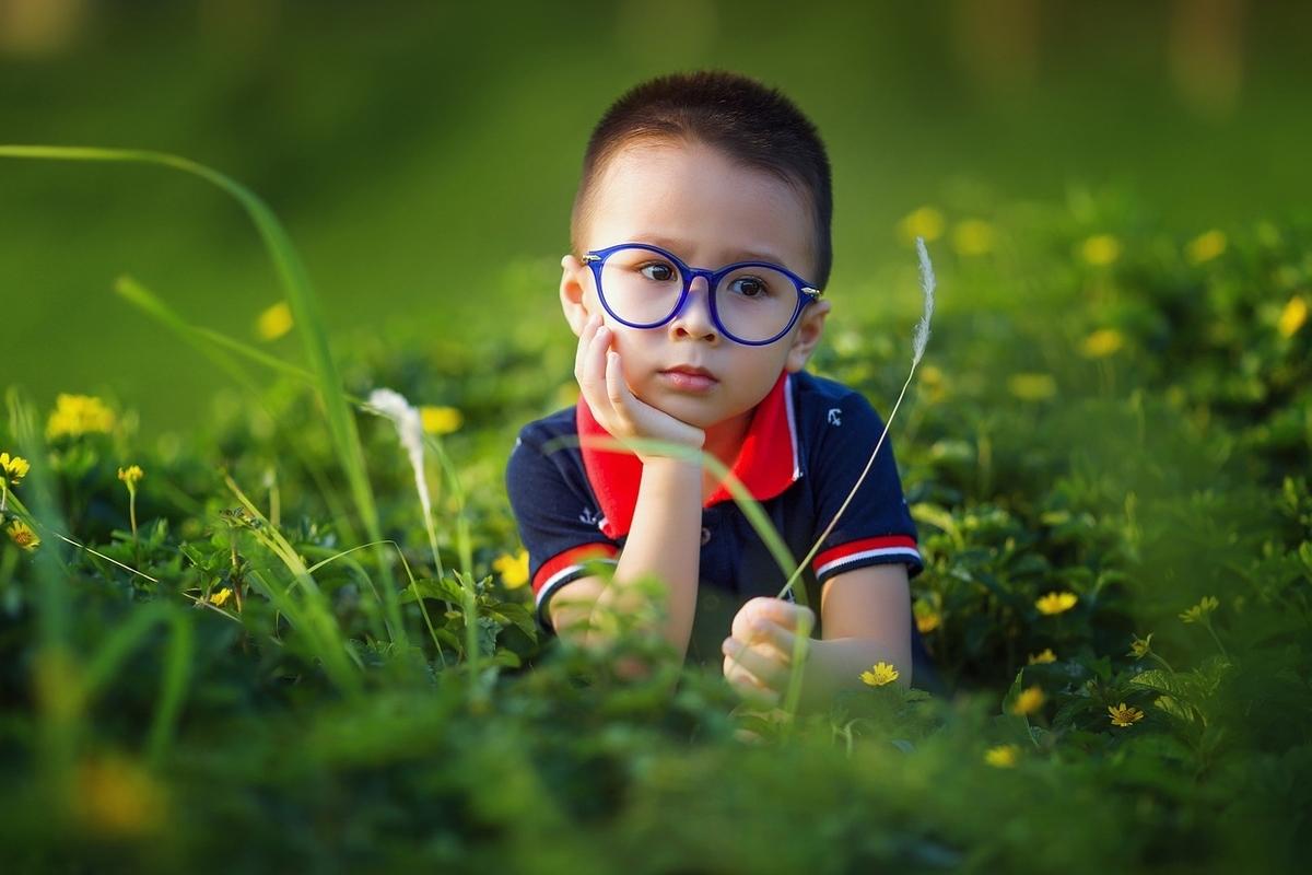 眼鏡をかけて考えている少年