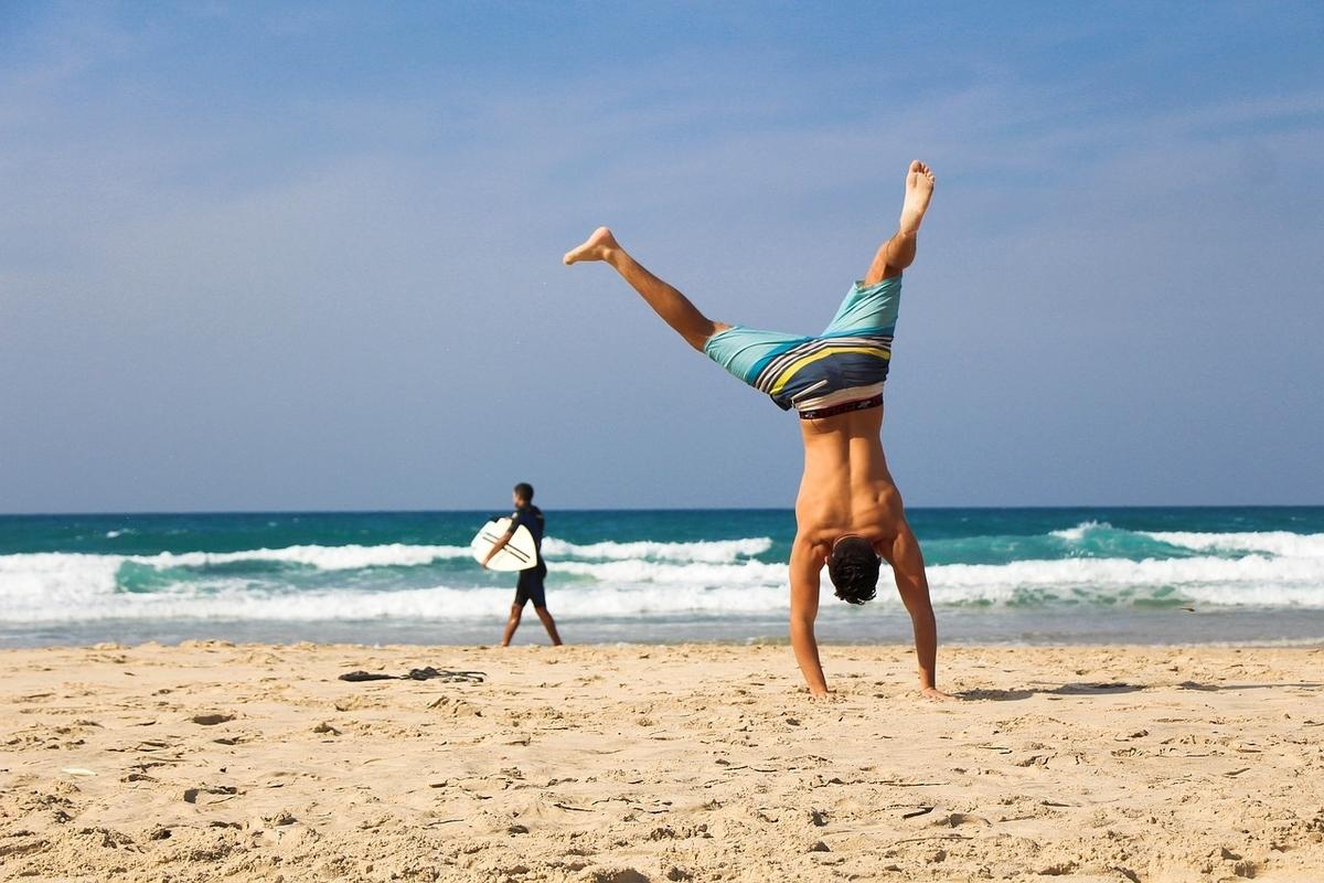 ビーチで逆立ちする男性