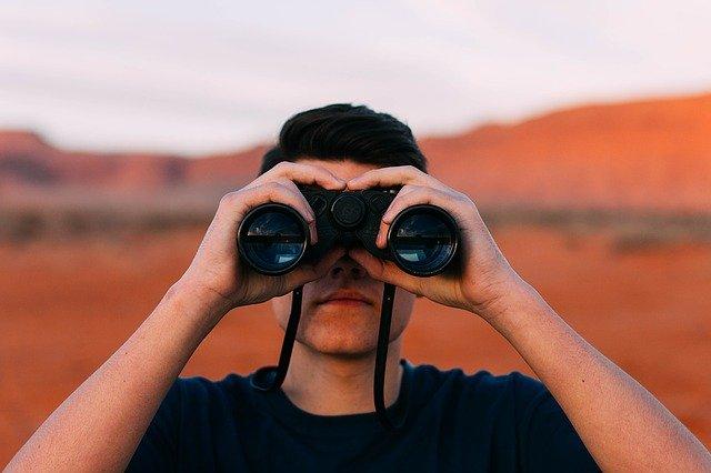 双眼鏡で覗く男性