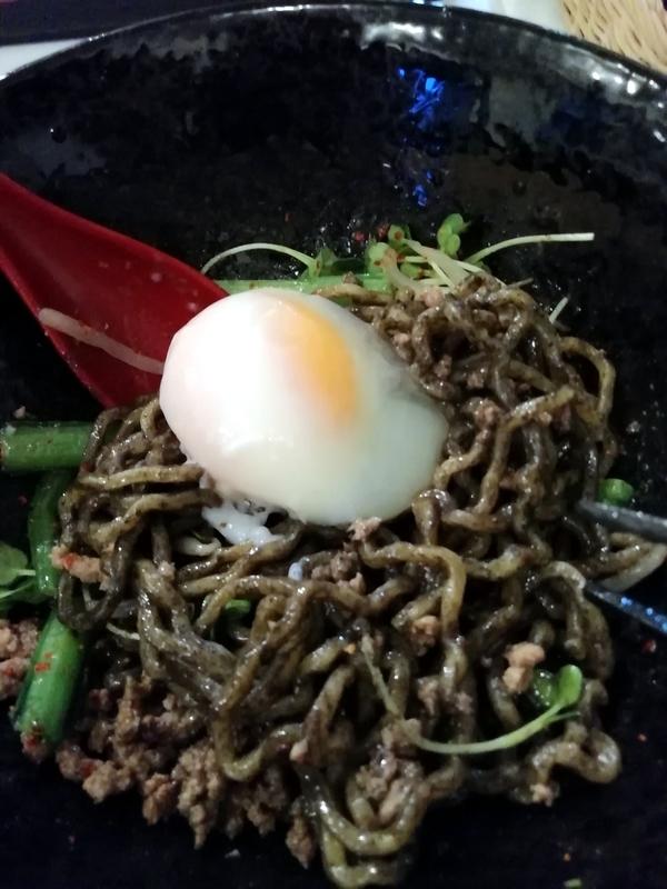 汁なし麺専門店 メンデザインさんの汁なし担々麺 黒に温玉を投入。