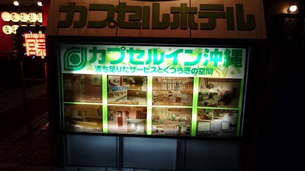 カプセルイン沖縄の建物の前に表示されている、施設の写真入りの案内看板
