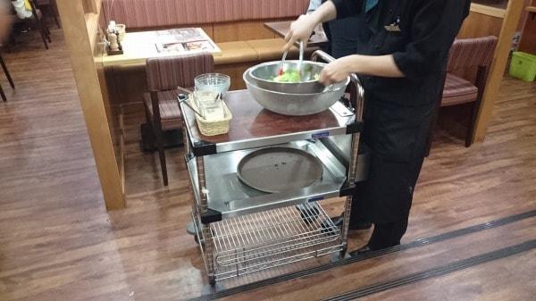 テーブルの横で大きなボウルを使い、サラダの準備中