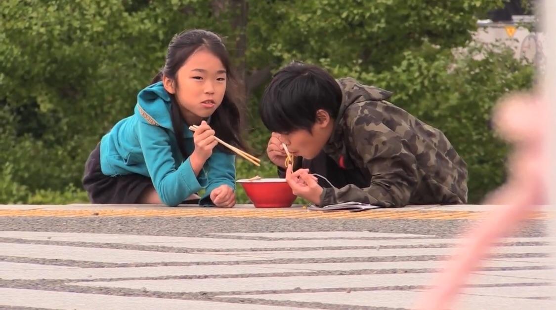 地べたに寝転んでタイヘンにお行儀よくラーメンを食す子どもたち。