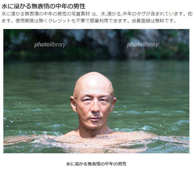水に浸かる無表情の中年の男性