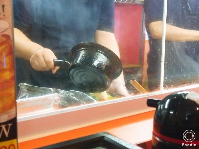 たっぷりの刻みニンニクに300℃近くまで熱した香味油で焼き上げる図