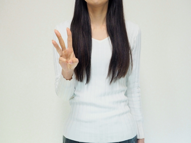 3本指を立てる女性バストアップ