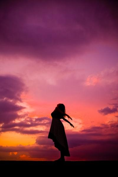 夕焼け空の中、腕を広げて天を仰ぐ女性のシルエット