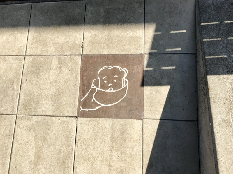 入り口前にあるパンが描かれたタイル