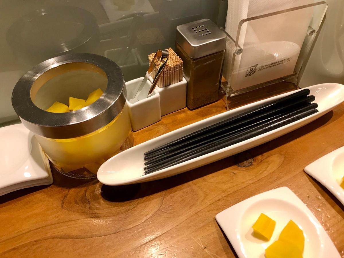 カウンターに置かれている箸、たくあんなど