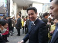 握手する前原誠司経済財政担当相(成城学園前)  後ろは小宮山洋子