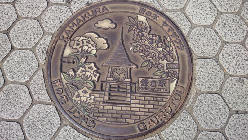 神奈川県鎌倉市のマンホール(鎌倉駅駅舎、ヤマザクラ、リンドウ)[カラー]