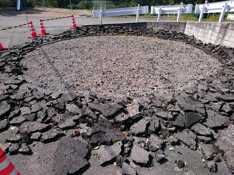 アスファルトが円形に剥がされた南部体育館横の駐車場