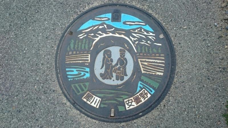 長野県安曇野市のマンホール(双体道祖神、北アルプス)[カラー]