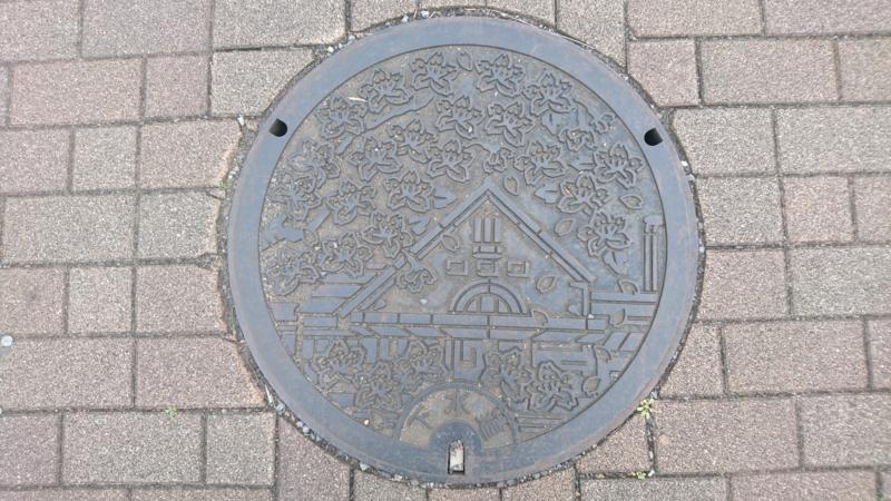 東京都国立市のマンホール(JR国立駅の駅舎と桜)