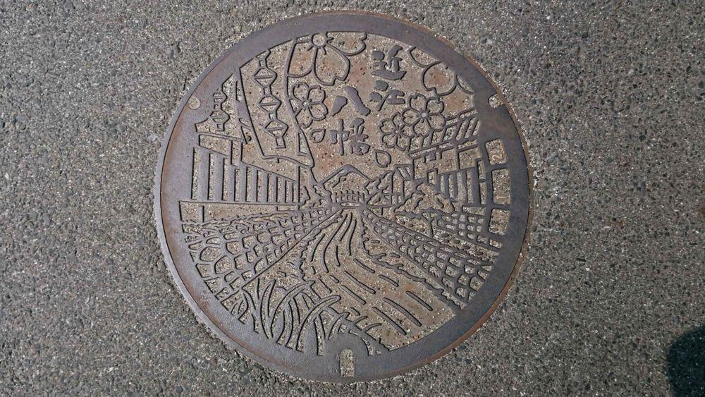 滋賀県近江八幡市のマンホール(八幡堀、八幡山、そろばん玉の柄の暖簾、サクラ)