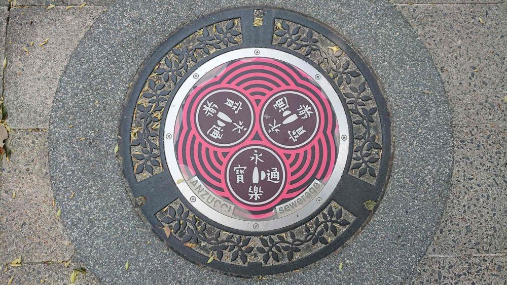 滋賀県近江八幡市のマンホール(旧安土町、まけずの鍔、永楽通宝銭)[カラー赤色]