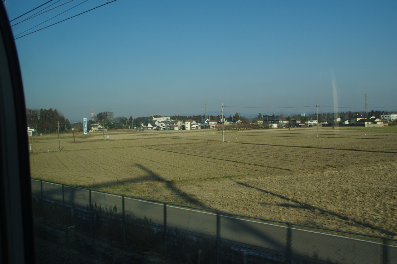 架線柱の影と田畑