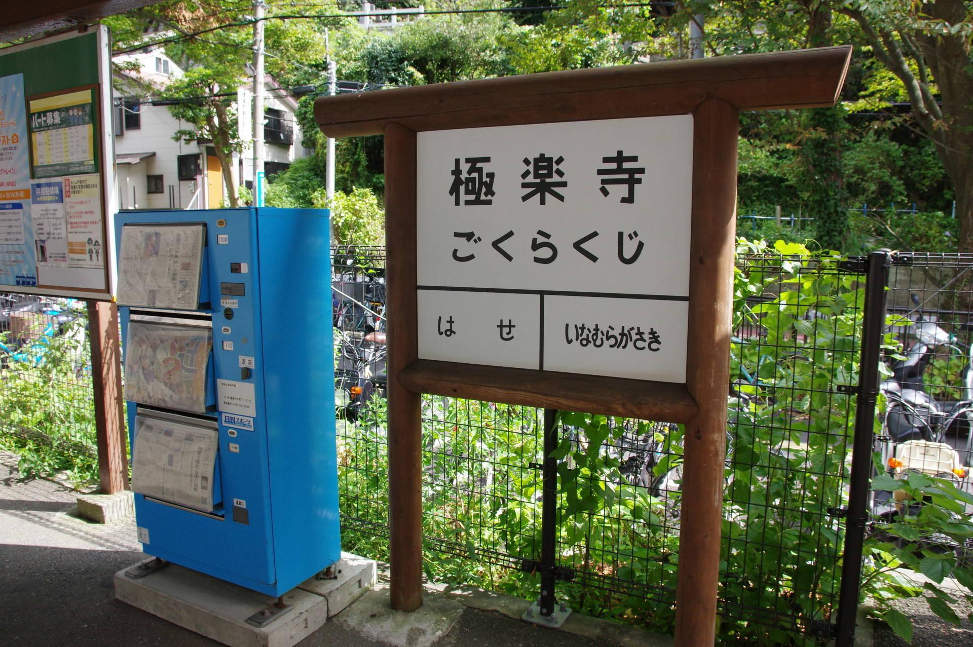 レトロなタイプの駅名標と水色の新聞自販機