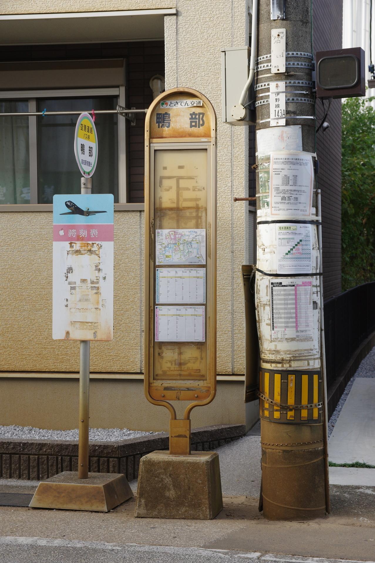 時刻表が貼られた電柱とバス停